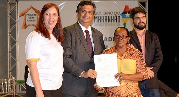A secretária de Estado das Cidades, Flávia Alexandrina, ao lado do governador Flávio Dino e do diretor da Caema, Davi Teles, entregam título de regularização fundiária.