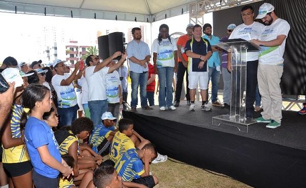 Governador Flávio Dino e o diretor da Caema, Davi Teles, assinam ordens de serviço, observados pelos atletas campeões do JEMs.