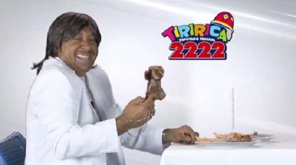 O deputado federal Tiririca usou roupa branca e peruca para parodiar Roberto Carlos no horário eleitoral.